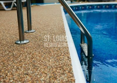pebble-stone epoxy pool deck in Missouri installed by local St. Louis Resurfacing, Inc. Decorative concrete resurfacing was performed.